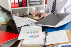 Overworked businessman. Businessman working at a untidy and cluttered desk Royalty Free Stock Photography