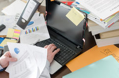 Overworked businessman. Businessman working at a untidy and cluttered desk Stock Photography
