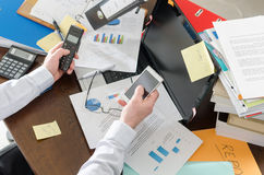 Overworked businessman. Businessman working at a untidy and cluttered desk Stock Photo