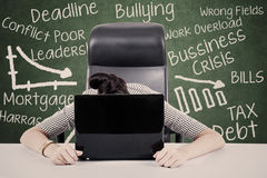 Overworked businesswoman. With her face on keyboard of laptop. Shot at workplace Stock Photos