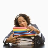 Overworked businesswoman. Businesswoman resting head on large stack of books and files with eyes closed Royalty Free Stock Images