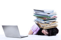 Overworked businesswoman with documents isolated. Depressed young businesswoman with a pile of documents on her head at office Royalty Free Stock Photos