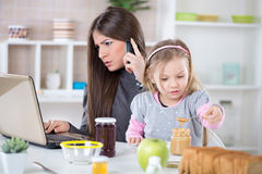 Overworked businesswoman at home. Overworked Business Woman and her little daughter in the morning. Mother read mail and make phone calls before going to work Stock Photos