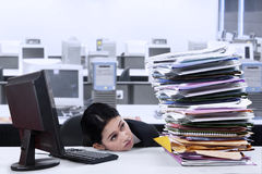 Overworked Businesswoman. Portrait of overworked businesswoman looking at pile of documents Stock Photo