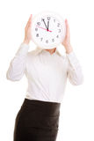 Overworked businesswoman showing clock. Time management. Overworked businesswoman showing clock. Busy woman covering her face isolated on white. Time management Royalty Free Stock Photography