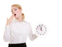 Overworked businesswoman showing clock and yawning. Time. Portrait of overworked businesswoman showing clock. Sleepy blond girl yawning isolated on white. Time Stock Images