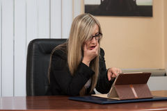 Overworked Businesswoman Sitting By Her Desk Royalty Free Stock Photography