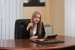 Overworked Businesswoman Sitting By Her Desk Stock Photography