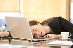 Overworked businesswoman sleeping at work. Overworked and tired businesswoman sleeping over a laptop in a desk at work in her office Stock Photo