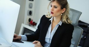 Overworked businesswoman staying in late. Overworked businesswoman staying in office late to work Royalty Free Stock Images