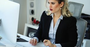 Overworked businesswoman staying in late. Overworked businesswoman staying in office late to work Stock Photos