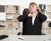 Overworked businesswoman stretching her neck. As she sits at her desk in the office to relieve the strain of sitting all day Royalty Free Stock Image