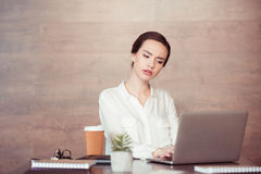 Overworked businesswoman using laptop at desk Royalty Free Stock Photography