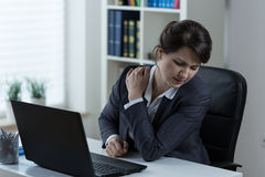 Overworked businesswoman. Young overworked businesswoman with pain in shoulder Stock Image