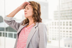 Overworked casual businesswoman having a headache. In the office Royalty Free Stock Images