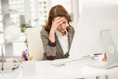 Overworked casual businesswoman working with computer Stock Photo