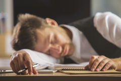 Overworked concept. Handsome young european businessman sleeping on office desk. Overworked concept Stock Images