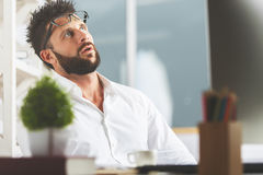 Overworked concept. Portrait of fed up young caucasian man with glasses on forehead sitting in office. Overworked concept Royalty Free Stock Images