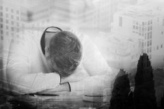 Overworked concept. Tired businessman at workplace on abstract city background. Double exposure. Overworked concept Royalty Free Stock Photo