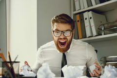Overworked depressed businessman screaming while sitting at his desk Stock Photo