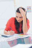 Overworked designer holding her head Royalty Free Stock Photography