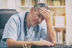 Overworked doctor in his office Royalty Free Stock Image