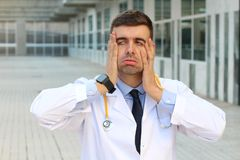 Overworked doctor looking very tired royalty free stock image