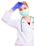 Overworked doctor or nurse woman in mask and lab coat isolated. Overworked woman in face mask and white lab coat. Tired doctor or nurse with stethoscope isolated Royalty Free Stock Photography