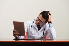 Overworked Doctor Sitting By His Desk Royalty Free Stock Photography