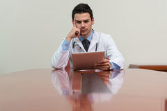 Overworked Doctor Sitting By His Desk Stock Photography