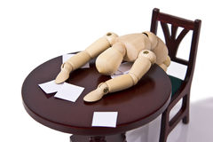 Overworked Employee. Exhausted wooden mannequin passed out over his desk. Paperwork is strewn about royalty free stock photos