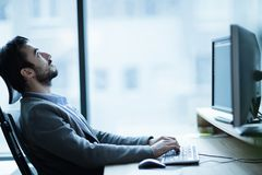 Overworked tired employee at workplace in office being unhappy. Overworked employee at workplace in office being unhappy Royalty Free Stock Image