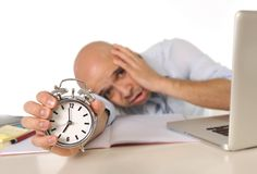 Overworked exhausted bald business man with computer and alarm clock Stock Images