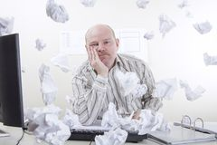 Overworked and Exhausted Businessman. Busy and overworked office worker with flying paper around in the office. To much work Royalty Free Stock Image