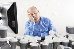 Overworked and exhausted businessman at office Royalty Free Stock Photos