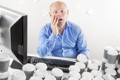 Overworked and exhausted businessman at the office Stock Images