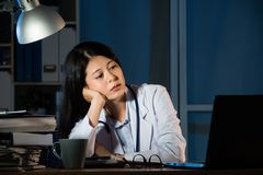 Overworked female doctor sitting beside desk. Tired and overworked female doctor sitting beside desk at office at night. beautiful mixed race asian chinese woman Royalty Free Stock Images