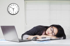Overworked female worker sleeping at workplace Stock Image