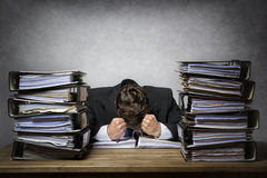 Overworked frustrated businessman. With lot of files on his desk Royalty Free Stock Image