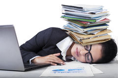 Overworked indian woman sleeping on desk. Tired female entrepreneur sleeping on desk with paperwork on her head Royalty Free Stock Images