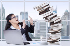 Overworked Indian worker and falling books Royalty Free Stock Image