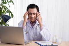 Overworked male doctor sat at his desk.  Stock Photography