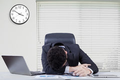 Overworked male worker sleeping in office. Tired male entrepreneur sleeping on desk after doing his job with laptop and documents in the office Royalty Free Stock Photos