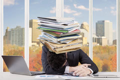 Overworked man with documents over his head Royalty Free Stock Photography