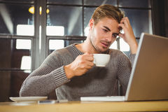 Overworked man drinking coffee and looking at laptop Stock Images