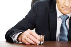 Overworked man drinking vodka in office Stock Photo