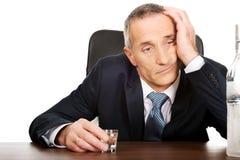 Overworked man drinking vodka in office.  Stock Photo