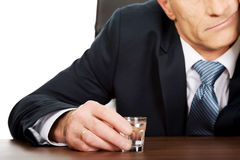 Overworked man drinking vodka in office.  Stock Image