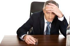 Overworked man drinking vodka in office. Overworked mature man drinking vodka in office Stock Photo