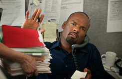 Overworked Man in Office. Black office worker with heavy workload on a phone call Stock Photos